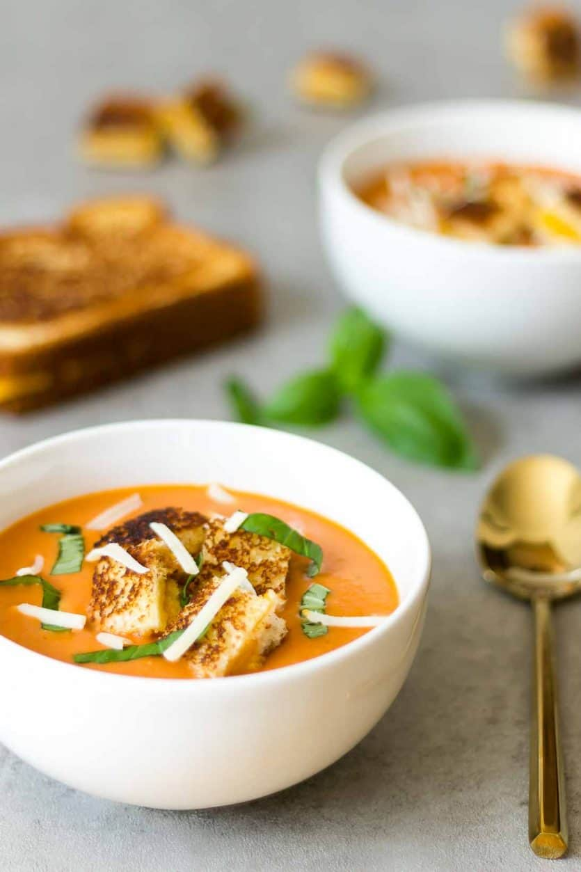 several bowls of creamy tomato homemade soup with grilled cheese in the background