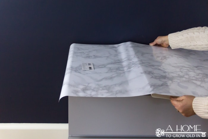 removing the backing from the contact paper while applying to ikea malm dresser