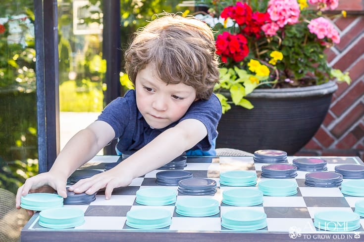 child playing on giant outdoor checkerboard