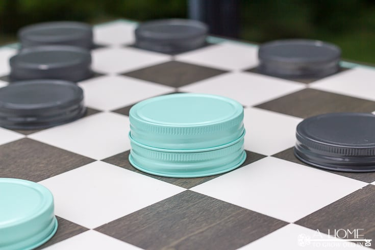 checkerboard with mason jar game pieces set up to play