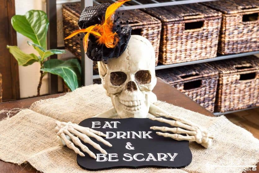 DIY halloween skull and bones centerpiece with eat drink and be scary sign