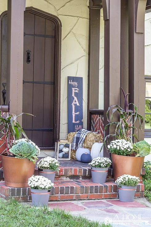 painted wood pallet sign on front porch with fall decor