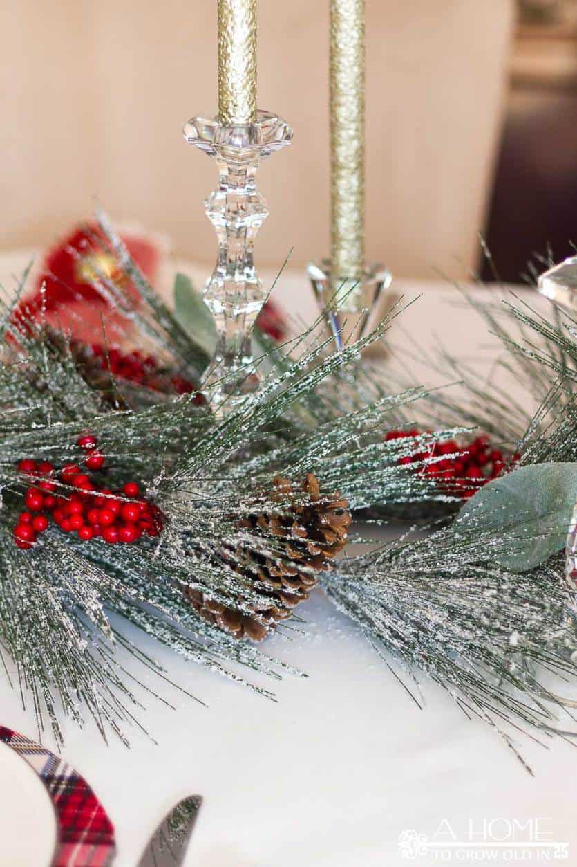 This simple and elegant Christmas tablescape has lots of fun elements like DIY plaid placemats, fringed napkins, and a snowy centerpiece.