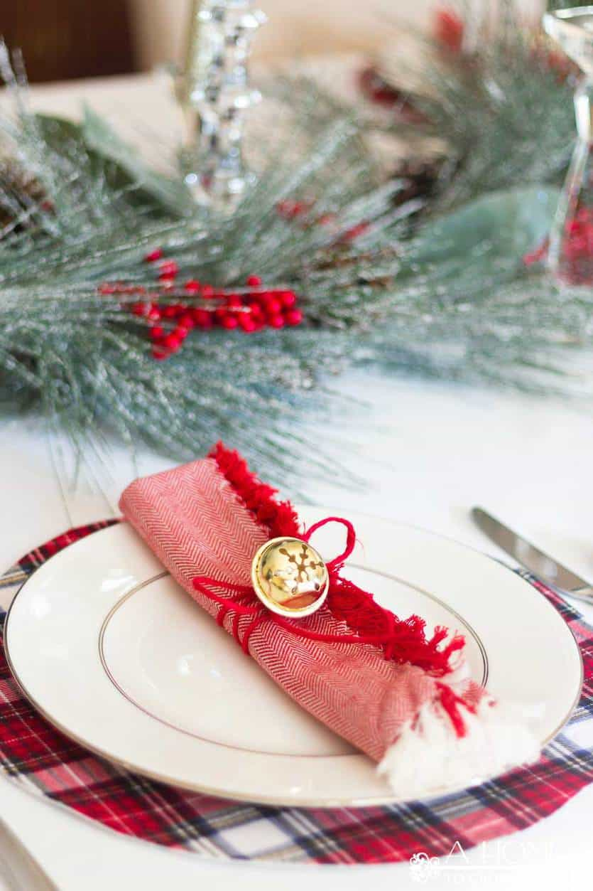 This simple and elegant Christmas tablescape has lots of fun ideas like DIY red and white plaid placemats, fringed napkins, and a beautiful snowy centerpiece. #christmastablescape #christmas
