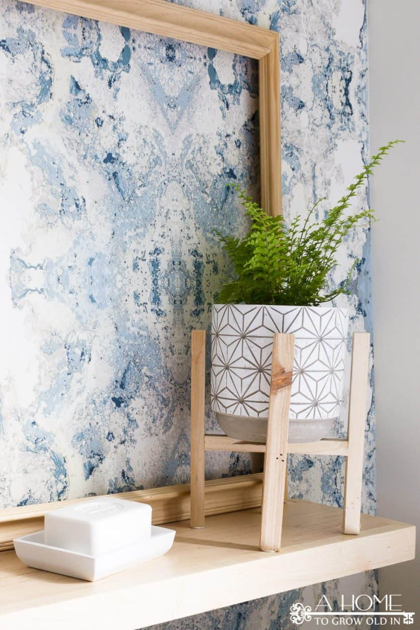 bathroom shelf with modern plant stand and anthropology wallpaper