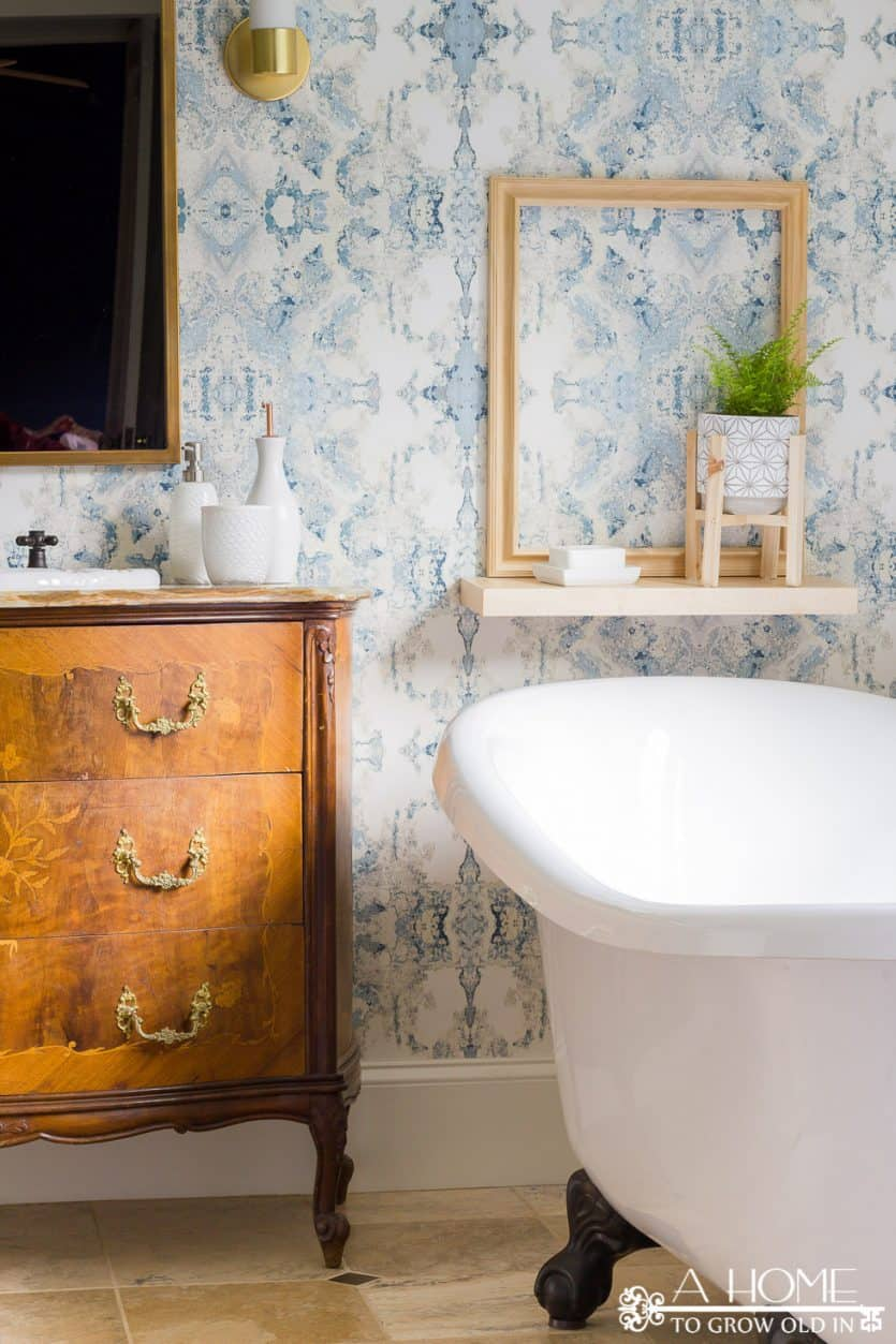modern bathroom makeover with Anthropology wallpaper, clawfoot bathtub and an antique vanity