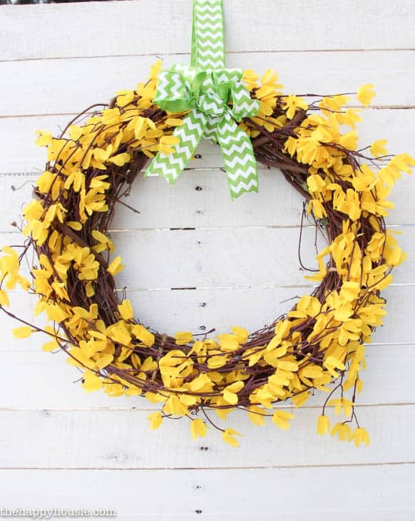 wreath made from dollar store materials and forsythia on a white wood background