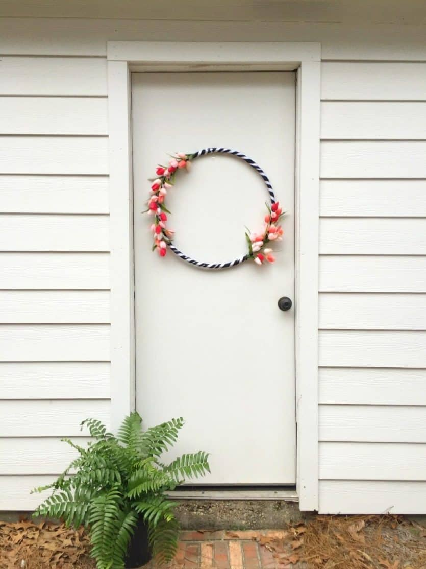 DIY wreath made from a hula hoop with tulips and black and white ribbon