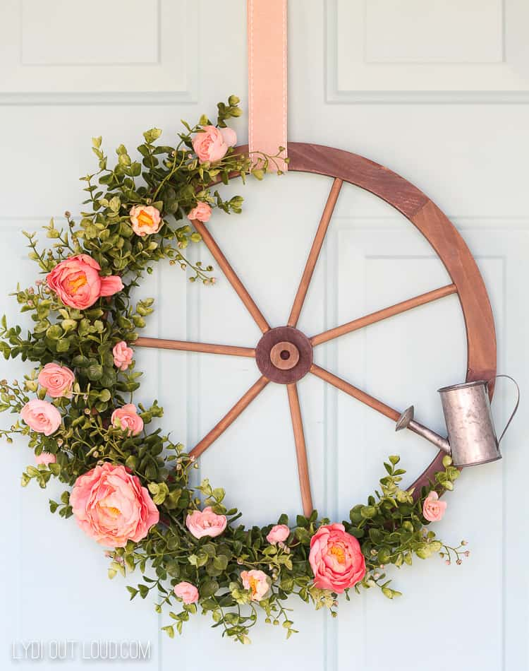 wagon wheel with peach peonies and boxwood used as a front door wreath