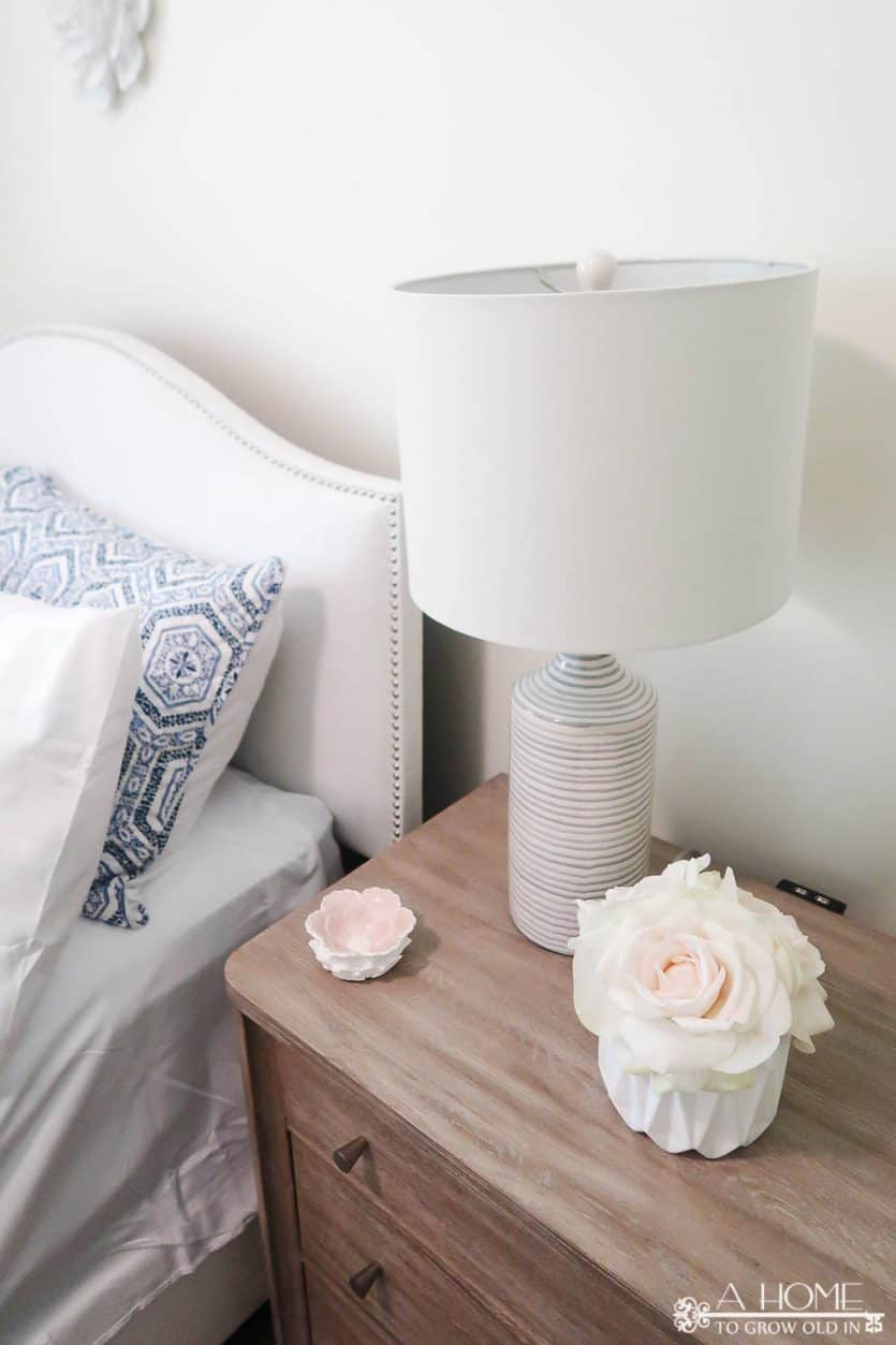 white upholstered bed with blue and white patterned quilt and wood nightstand with lamp
