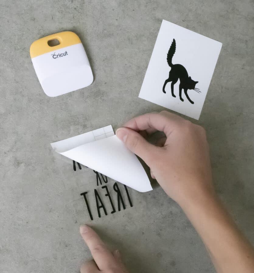 peeling Cricut transfer tape liner off design