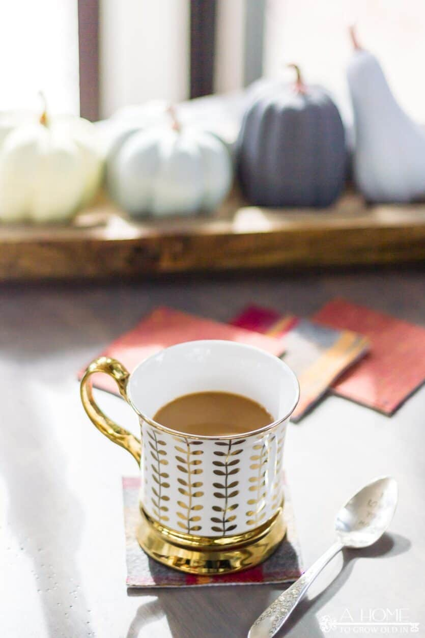 a cup of coffee on a plaid flannel coaster with pumpkins in the background
