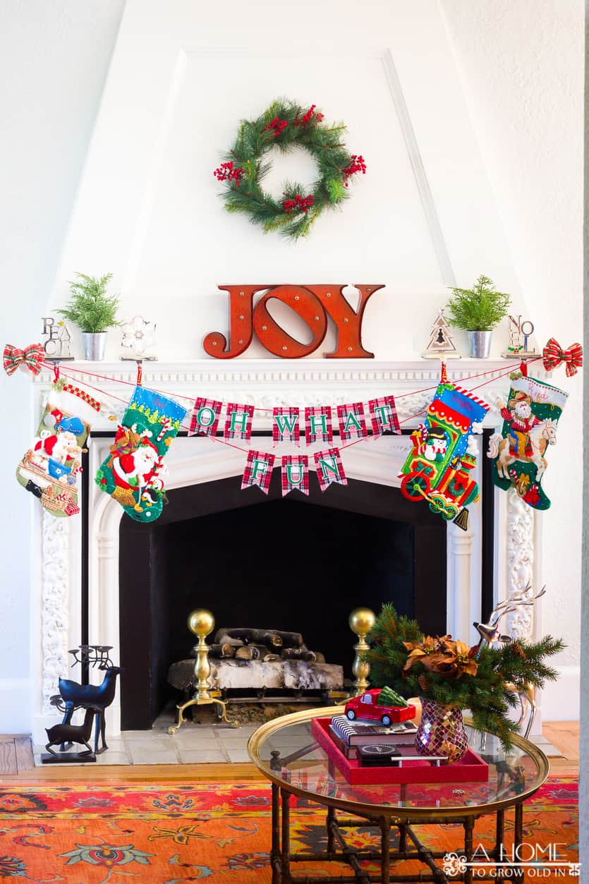 Oh What Fun DIY fabric Christmas banner hanging from a fireplace mantle with Christmas stockings