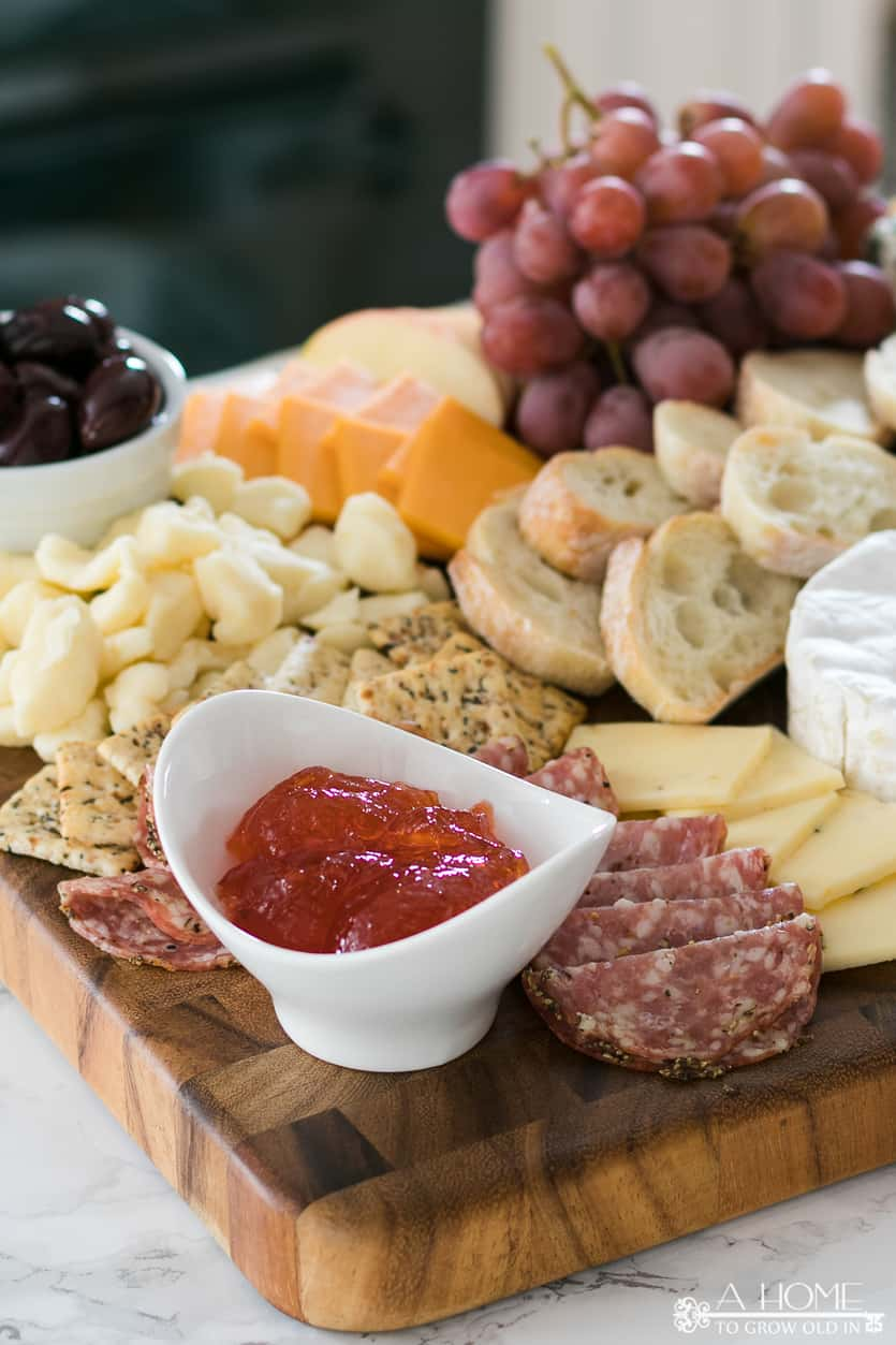 pepper jam in a bowl surrounded by cheese and crackers on a cheese board