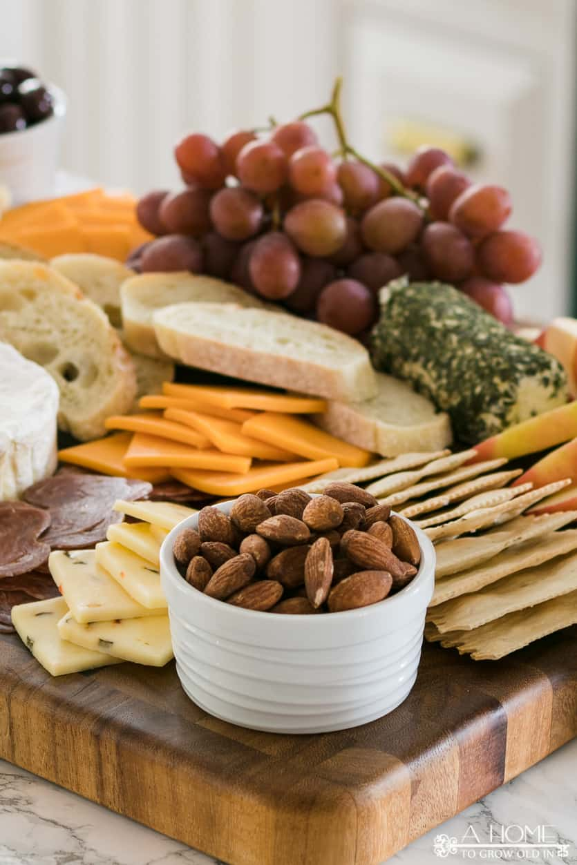 bowl of almonds surrounded by cheese and crackers on a cheeseboard