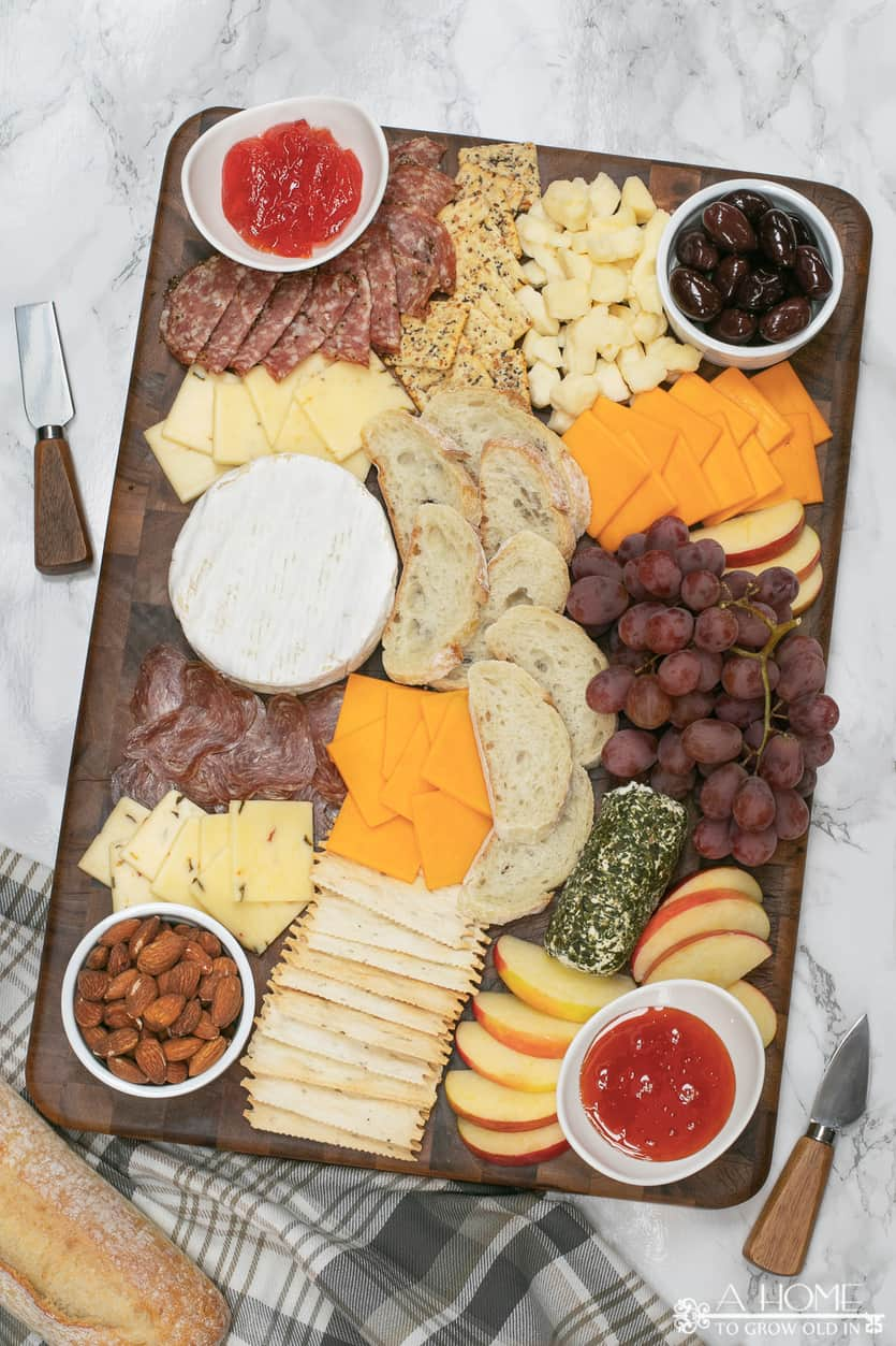 cheeseboard with salami, cheddar, brie, pepper jack, olives, pepper jam, goat cheese, grapes and apples
