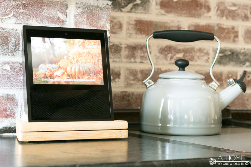 echo show with alexa on a kitchen countertop with a kettle in the background