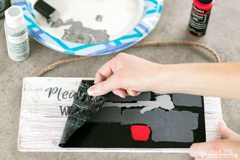peeling vinyl off painted wooden sign