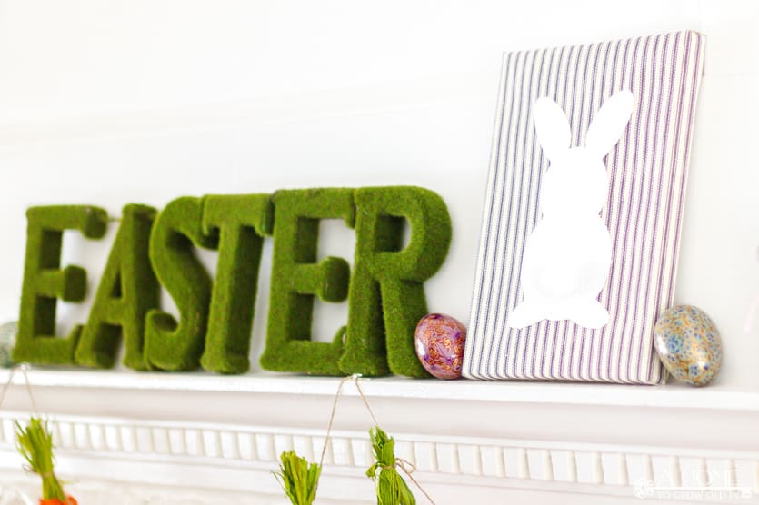 fireplace mantel decorated for spring or Easter with a DIY fabric wrapped bunny canvas