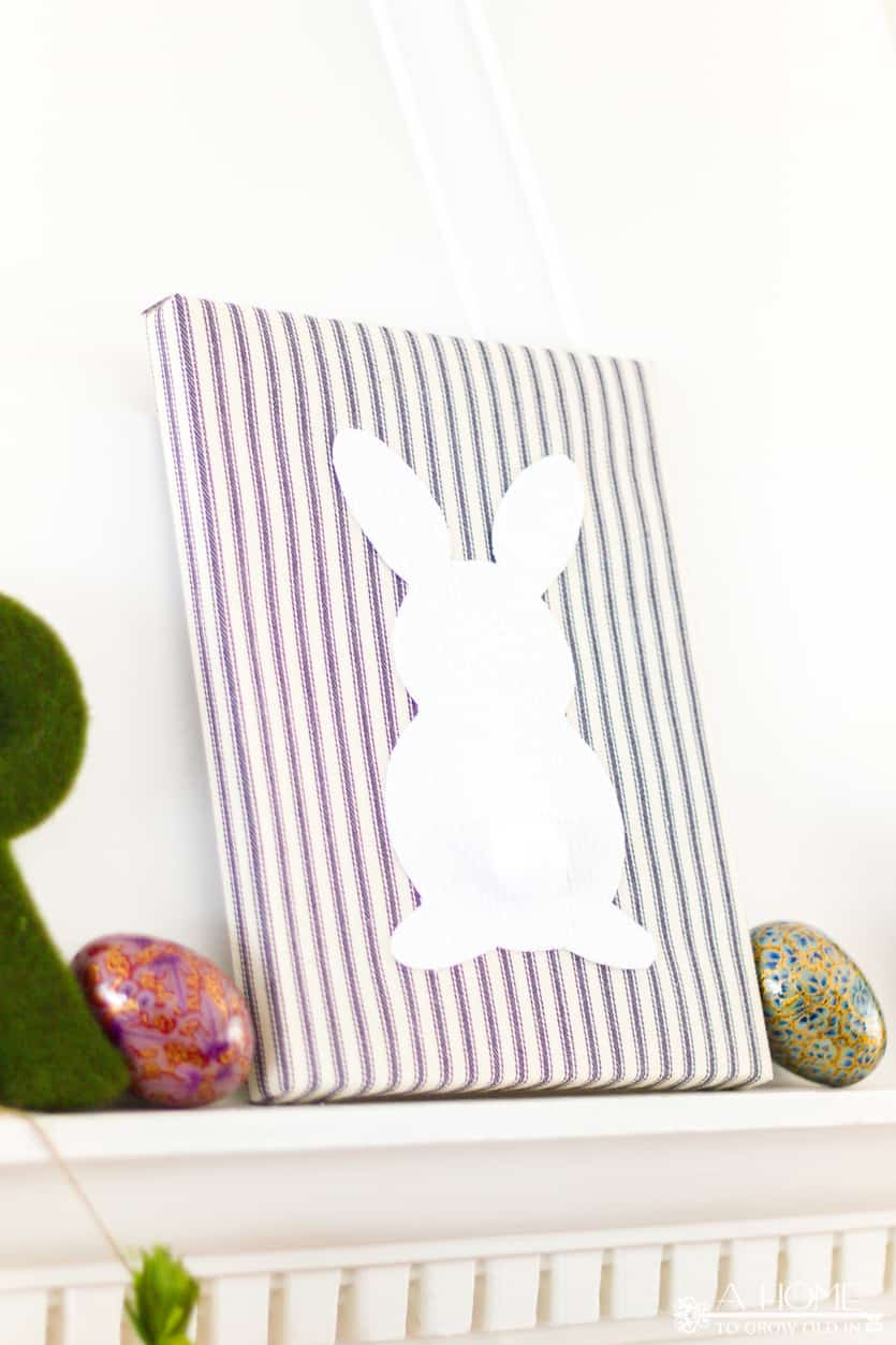 fireplace mantel decorated for spring or Easter with a DIY fabric wrapped bunny canvas art