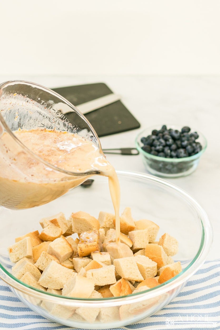 milk mixture pouring into bread cubes