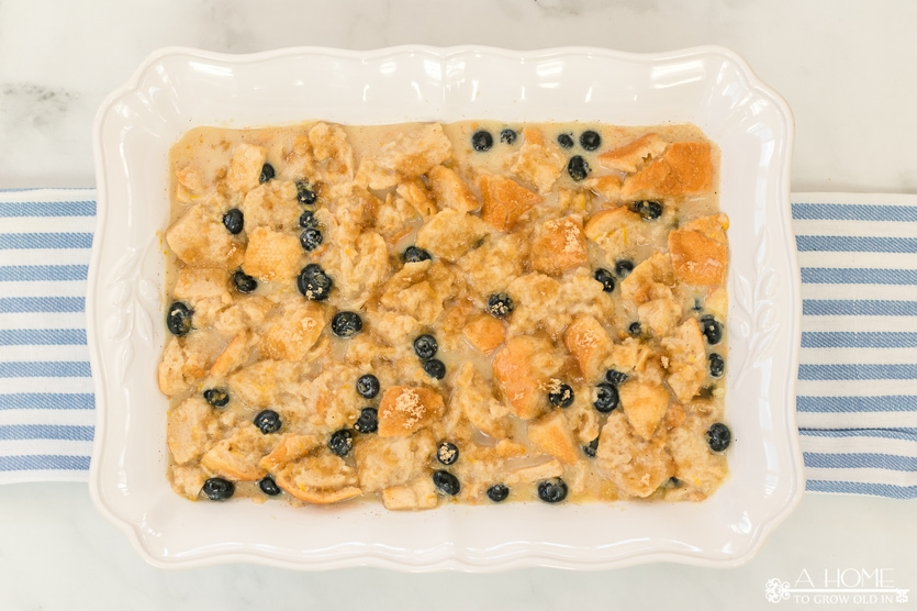 uncooked lemon blueberry bread pudding in a baking dish