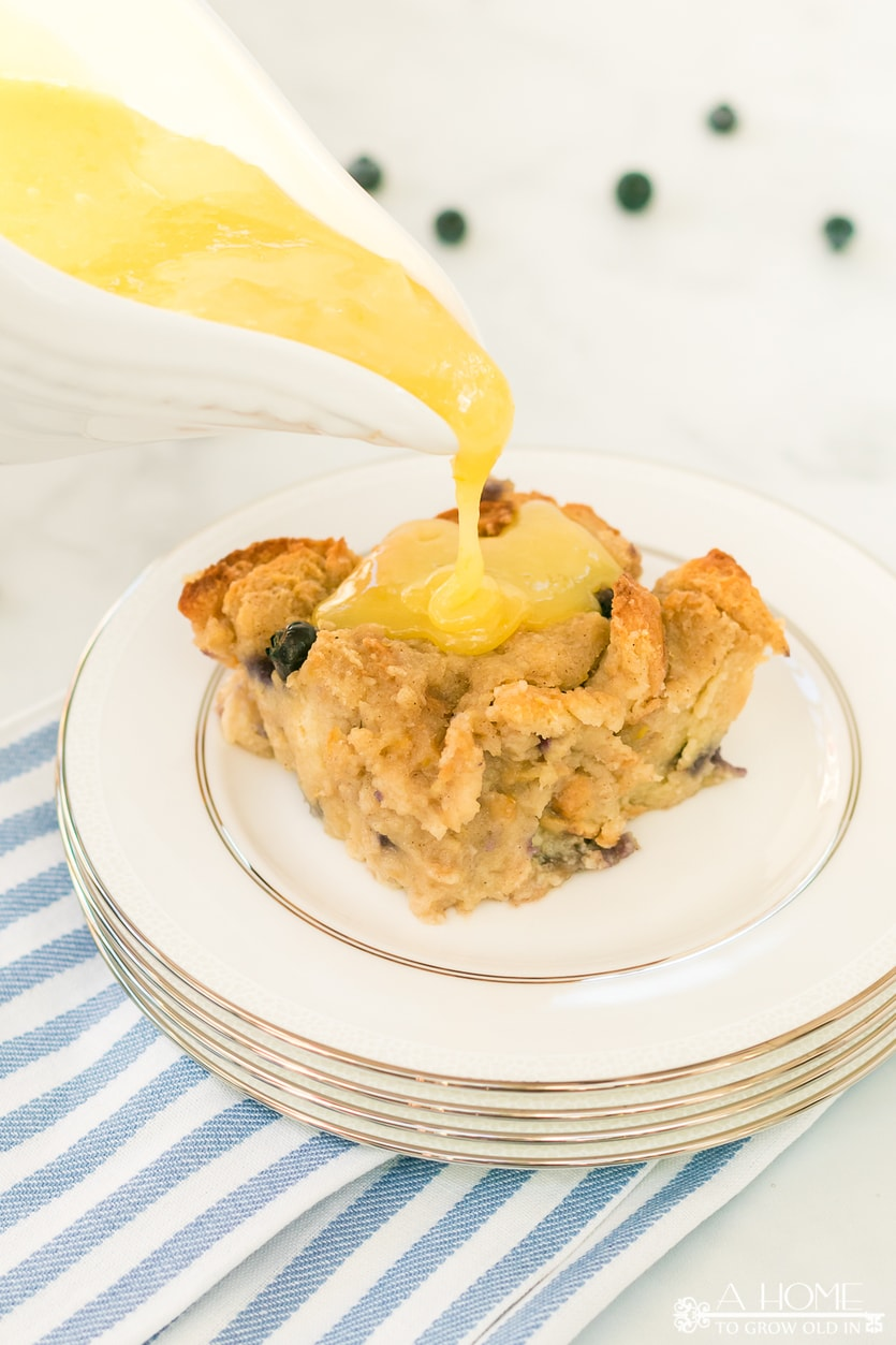lemon blueberry bread pudding on a plate with lemon curd sauce poured on top