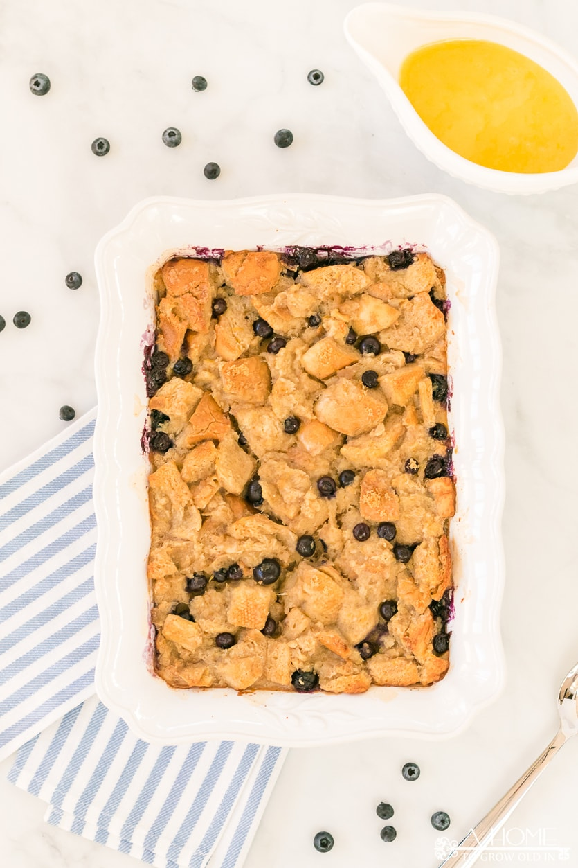 lemon blueberry bread pudding in a baking dish with lemon curd sauce in a pitcher
