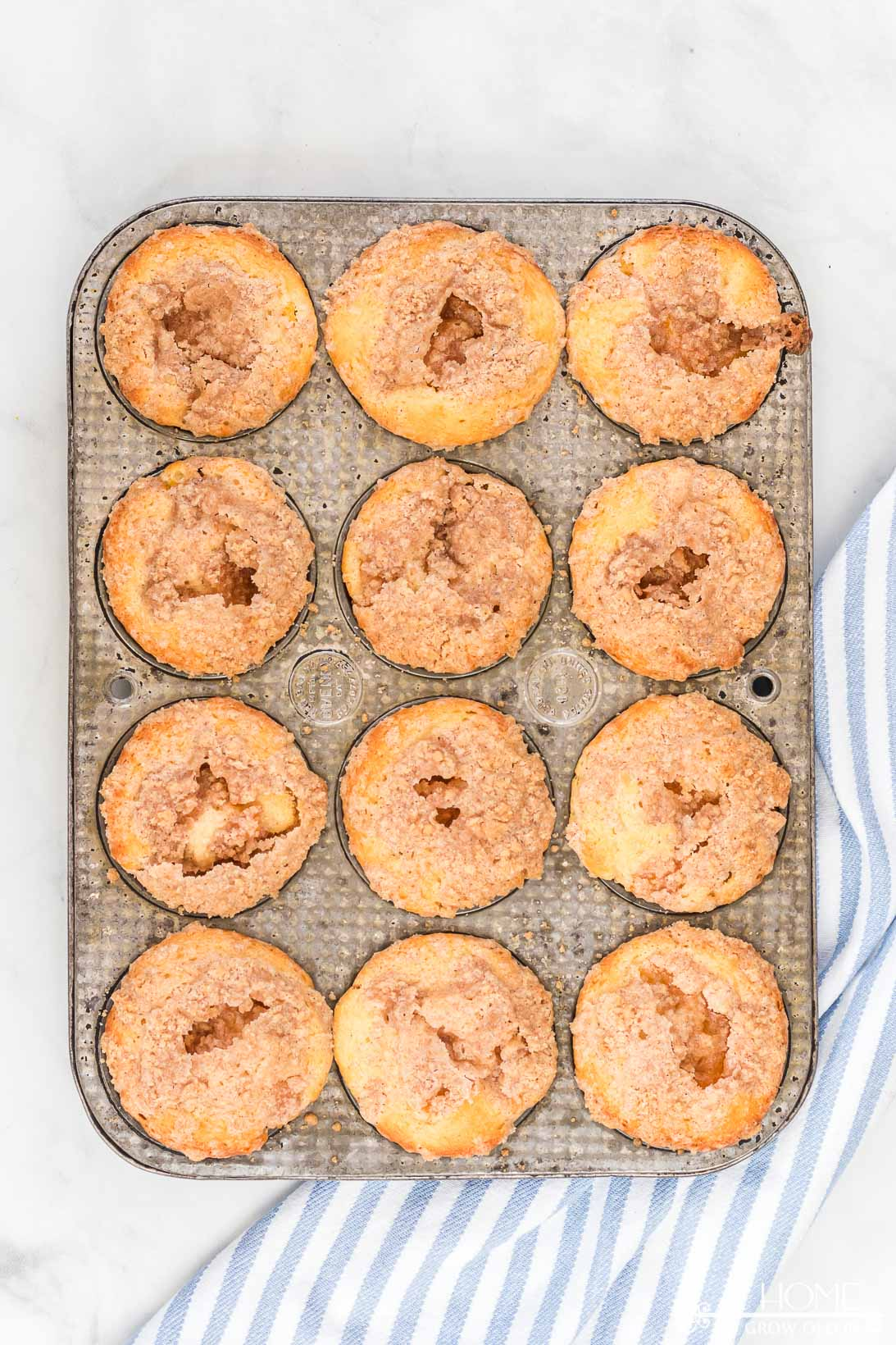 freshly baked peach cobbler muffins still in a muffin tin